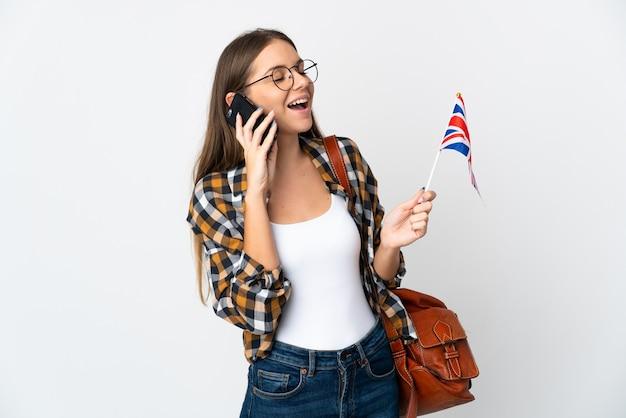 Молодая литовская женщина держит флаг соединенного королевства на белом фоне, разговаривает по мобильному телефону