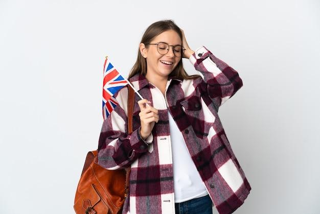 笑って白い背景で隔離のイギリス国旗を保持している若いリトアニアの女性