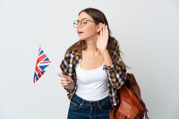 Молодая литовская женщина, держащая флаг соединенного королевства на белом фоне, слушает что-то, положив руку на ухо