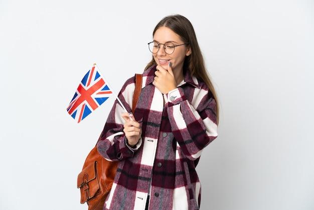 横を見て笑っている白い背景で隔離のイギリス国旗を保持している若いリトアニアの女性