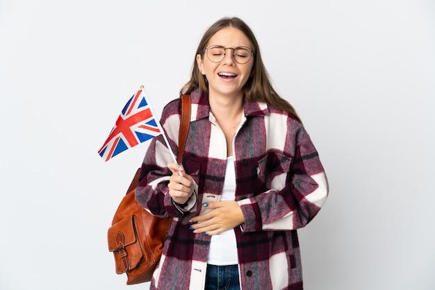 たくさん笑って白い背景で隔離のイギリス国旗を保持している若いリトアニアの女性