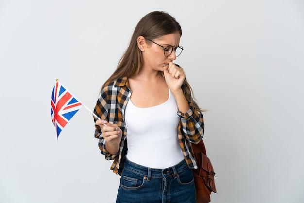 기침을 많이하는 흰 벽에 고립 된 영국 국기를 들고 젊은 리투아니아 여자
