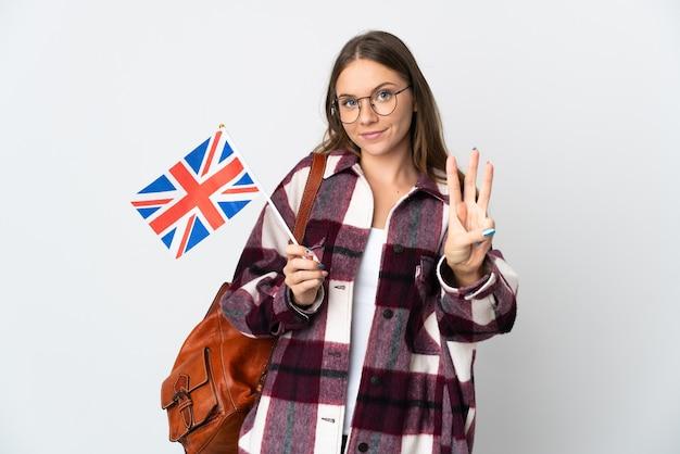 행복하고 손가락으로 세 세 흰 벽에 고립 된 영국 국기를 들고 젊은 리투아니아 여자