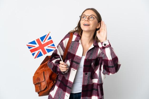 귀에 손을 넣어 뭔가를 듣고 흰 벽에 고립 된 영국 국기를 들고 젊은 리투아니아 여자