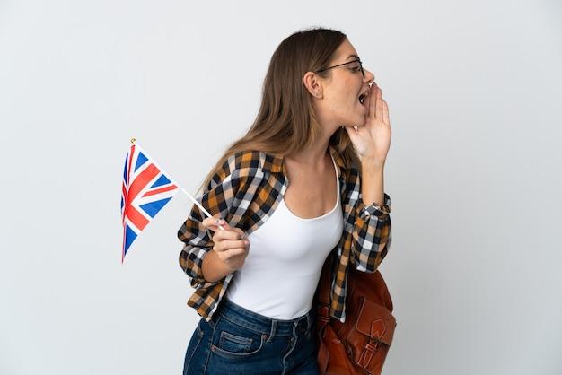 Молодая литовская женщина с флагом соединенного королевства изолирована на белой стене и кричит с широко открытым ртом