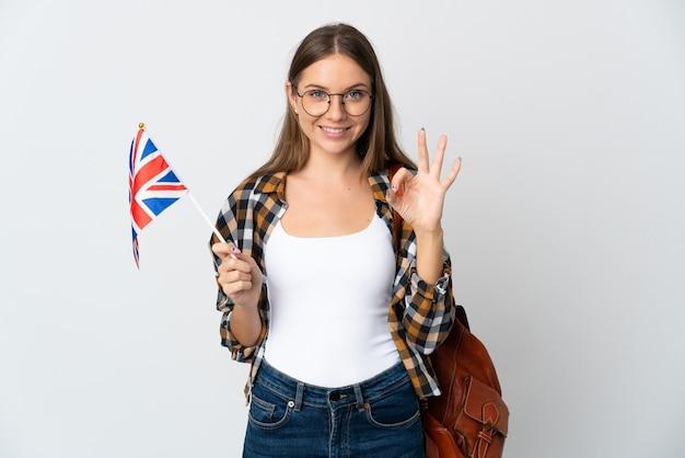両手でokサインを示す白い壁に分離されたイギリスの旗を保持している若いリトアニアの女性