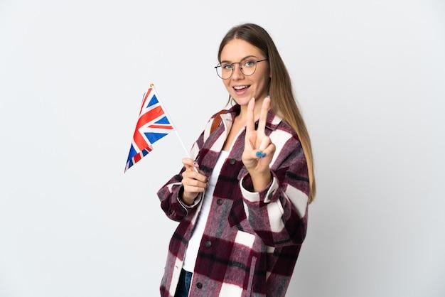 笑顔で勝利のサインを示す白い壁に分離されたイギリスの旗を保持している若いリトアニアの女性