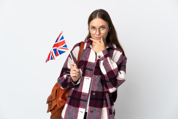 Молодая литовская женщина, держащая флаг соединенного королевства, изолированная на белой стене, думает