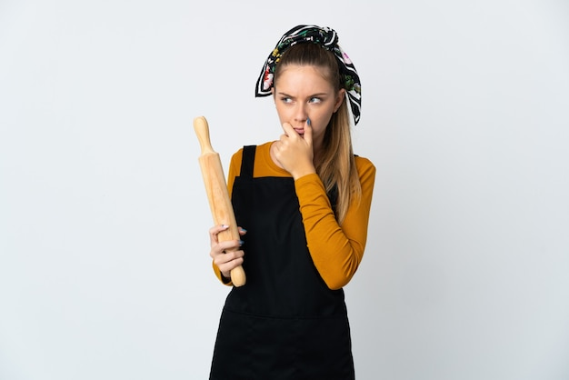 Young lithuanian woman holding a rolling pin isolated on white background
