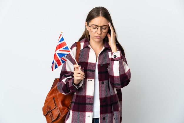 Young lithuanian woman holding an united kingdom flag isolated on white background with headache
