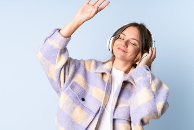 Young lithuanian woman isolated on blue background listening music and dancing