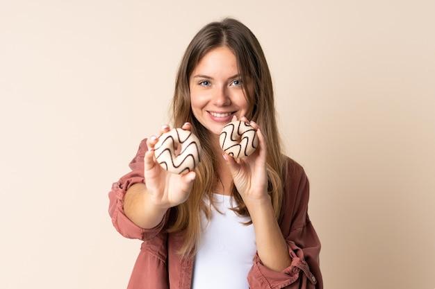 幸せな表情でドーナツを保持しているベージュの背景に分離された若いリトアニアの女性