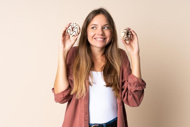ドーナツを保持しているベージュの背景に分離された若いリトアニアの女性