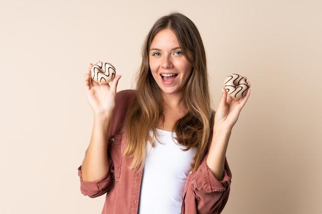 幸せな表情でドーナツを保持しているベージュに分離された若いリトアニアの女性