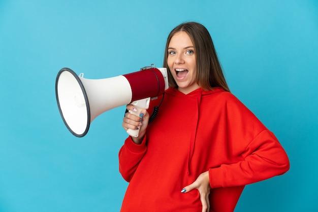 Молодая литовская женщина изолирована на синем фоне с мегафоном и улыбается