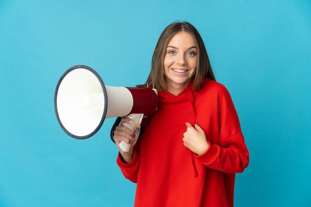 Молодая литовская женщина изолирована на синем фоне с мегафоном и с удивленным выражением лица