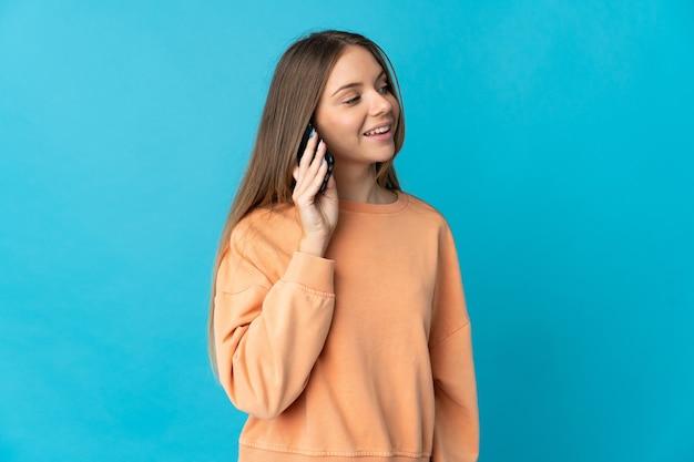 Молодая литовская женщина изолирована на синем фоне, разговаривая с кем-то по мобильному телефону