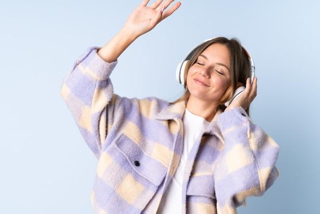 Молодая литовская женщина изолирована на синем фоне, слушает музыку и танцует