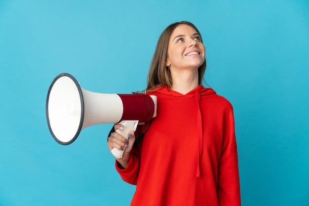 Молодая литовская женщина изолирована на синей стене с мегафоном и смотрит вверх, улыбаясь