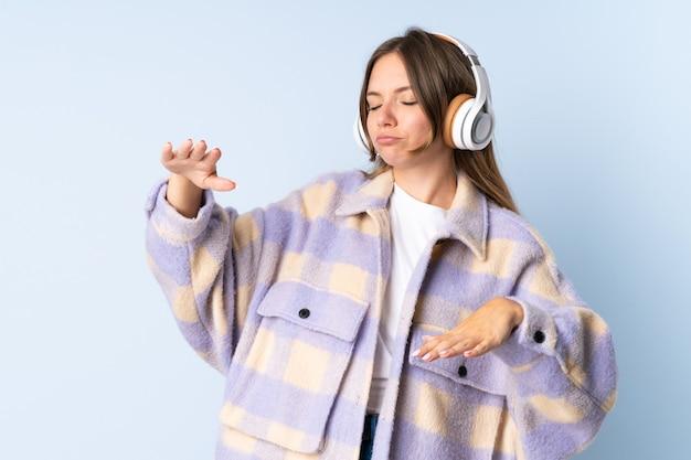 Молодая литовская женщина изолирована на синей стене, слушает музыку и танцует