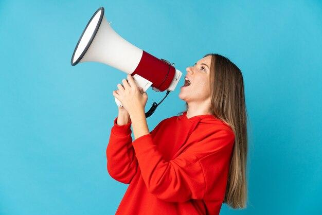 측면 위치에서 뭔가를 발표하기 위해 확성기를 통해 외치는 파란색 벽에 고립 된 젊은 리투아니아 여자