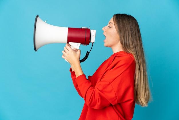 Молодая литовская женщина изолирована на синей стене и кричит в мегафон, чтобы объявить что-то в боковом положении