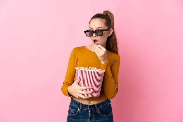 젊은 리투아니아 여자 3d 안경 분홍색 벽에 격리하고 측면을 보면서 팝콘의 큰 양동이를 들고