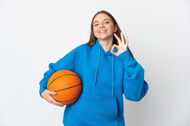 バスケットボールをし、okサインを作る白い壁に孤立した若いリトアニアの女性