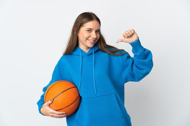 バスケットボールをしている白い壁に孤立し、自分自身を誇りに思っている若いリトアニアの女性