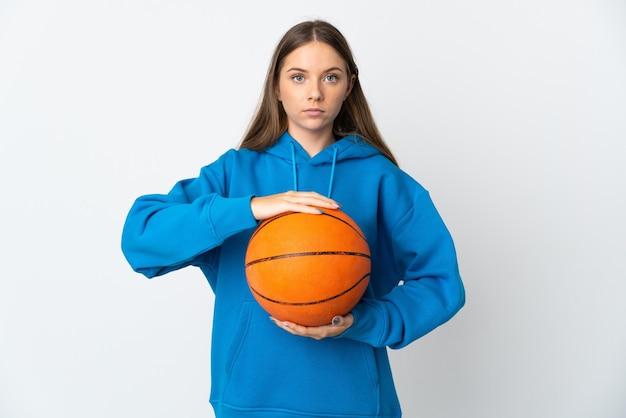 バスケットボールをしている白い壁に孤立した若いリトアニアの女性