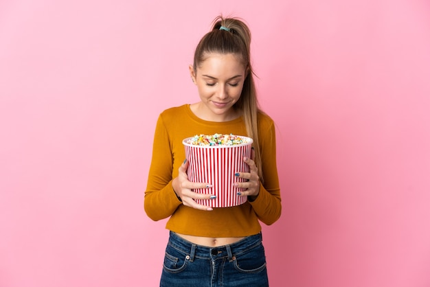 Young lithuanian woman isolated on pink background holding a big bucket of popcorns