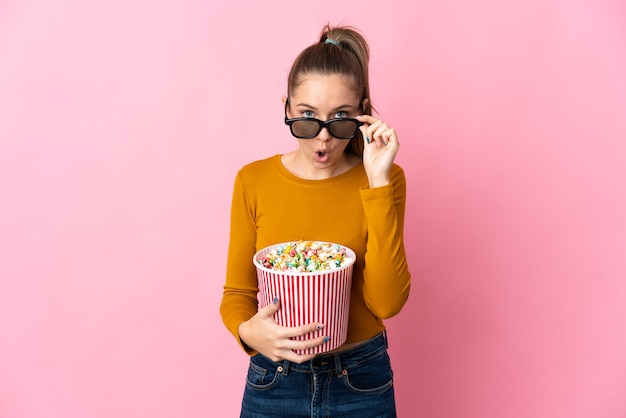 Young lithuanian woman isolated on pink background surprised with 3d glasses and holding a big bucket of popcorns