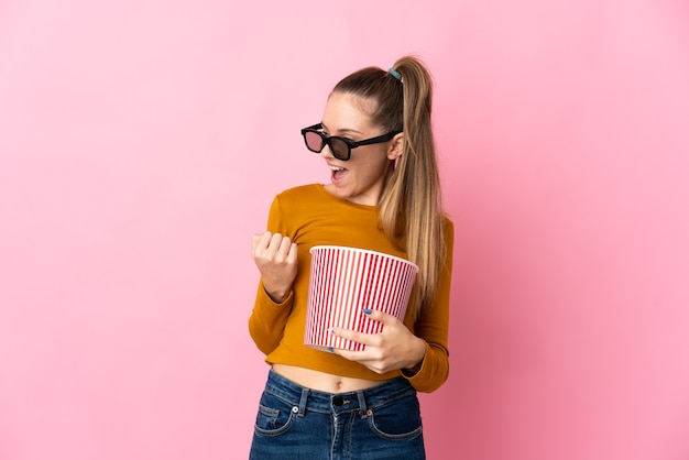 Young lithuanian woman isolated on pink background with 3d glasses and holding a big bucket of popcorns while looking side