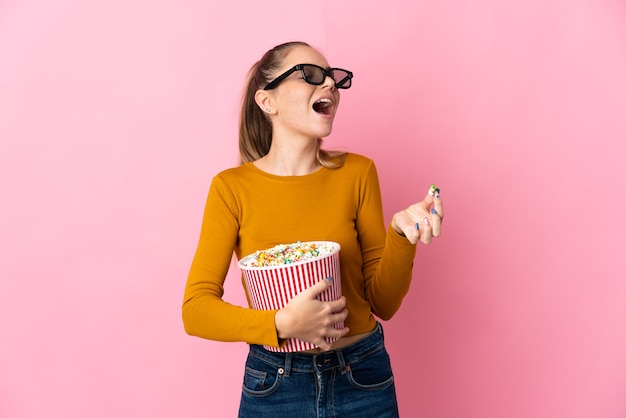 Young lithuanian woman isolated on pink background with 3d glasses and holding a big bucket of popcorns