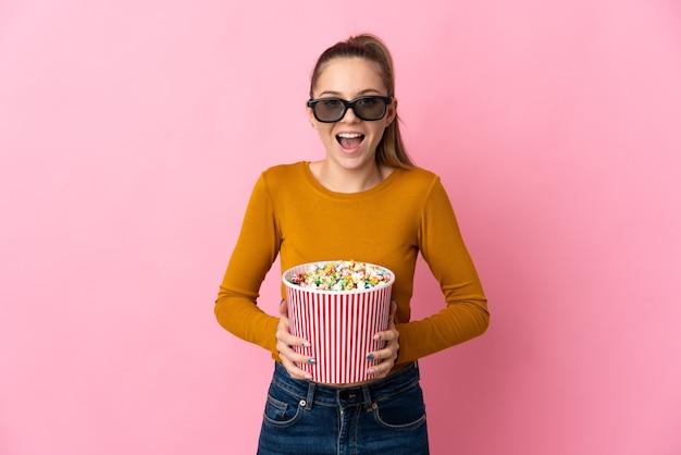 Young lithuanian woman isolated with 3d glasses and holding a big bucket of popcorns