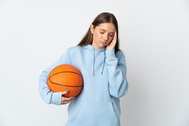 흰색 배경에 두통이 있는 농구를 하는 젊은 리투아니아 여자