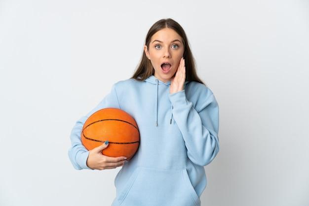 Молодая литовская женщина играет в баскетбол на белом фоне с удивленным и шокированным выражением лица