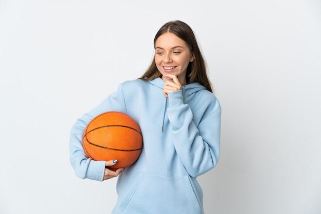 젊은 리투아니아 여자 농구 측면을 찾고 웃 고 흰 벽에 고립