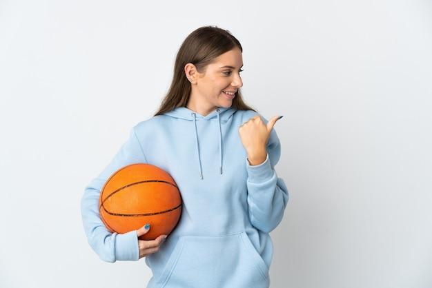 製品を提示する側を指している白い壁に分離されたバスケットボールをしている若いリトアニアの女性
