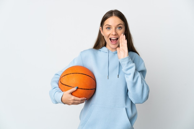 Молодая литовская женщина играет в баскетбол изолирована на белой стене и кричит с широко открытым ртом