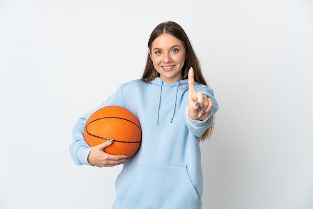 白い壁に隔離されたバスケットボールをしている若いリトアニアの女性が指を見せて持ち上げる