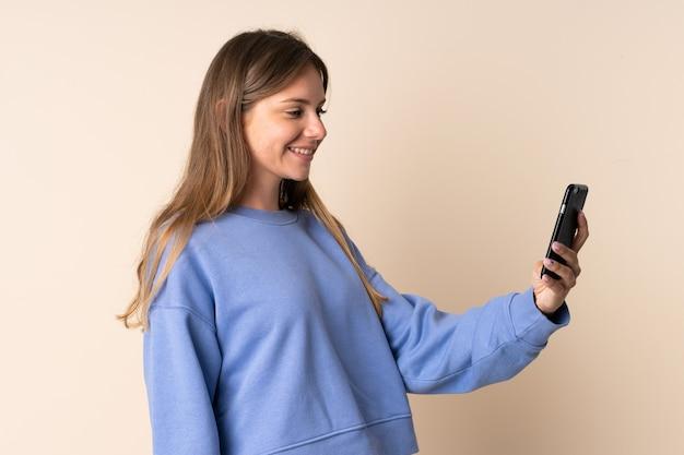 幸せな表情でベージュの背景に分離された携帯電話を使用して若いリトアニアの女性