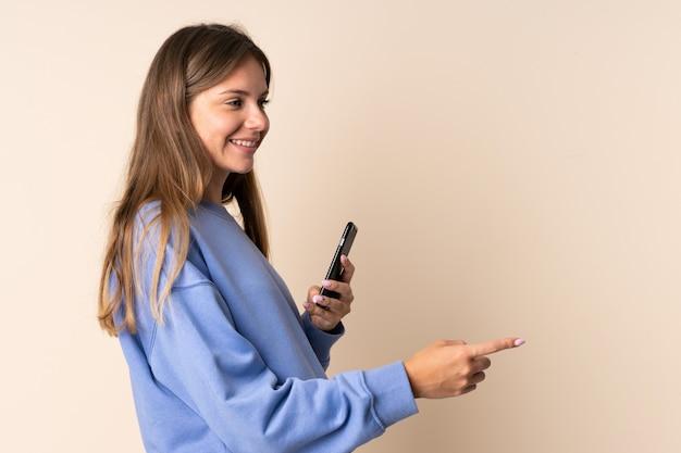 Молодая литовская женщина с помощью мобильного телефона изолирована на бежевом, указывая в сторону, чтобы представить продукт