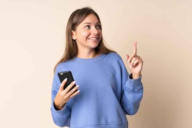 指を持ち上げながら解決策を実現しようとしているベージュの壁に分離された携帯電話を使用して若いリトアニアの女性