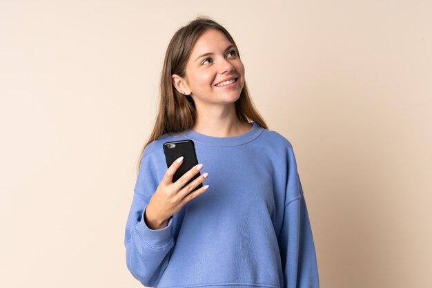 笑顔で見上げるベージュの壁に分離された携帯電話を使用して若いリトアニアの女性