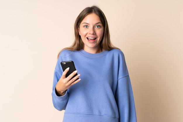 Молодая литовская женщина разговаривает по мобильному телефону, изолирована на бежевом, с удивленным и шокированным выражением лица