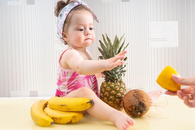 Молодая маленькая девочка сидит на поверхности стола среди тропических фруктов