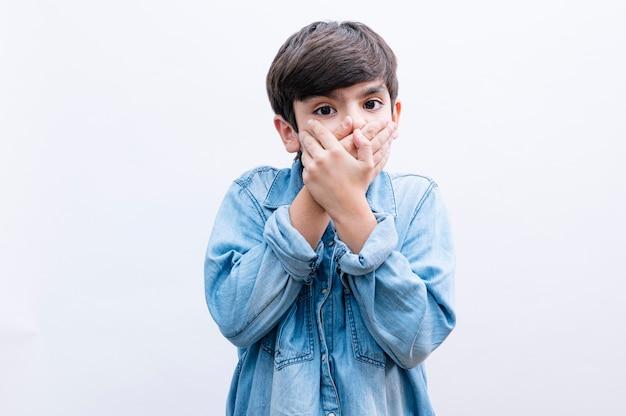 Молодой маленький мальчик прикрывает рот рукой, потрясенный позором за ошибку, выражение страха, испуганный в тишине, секретная концепция