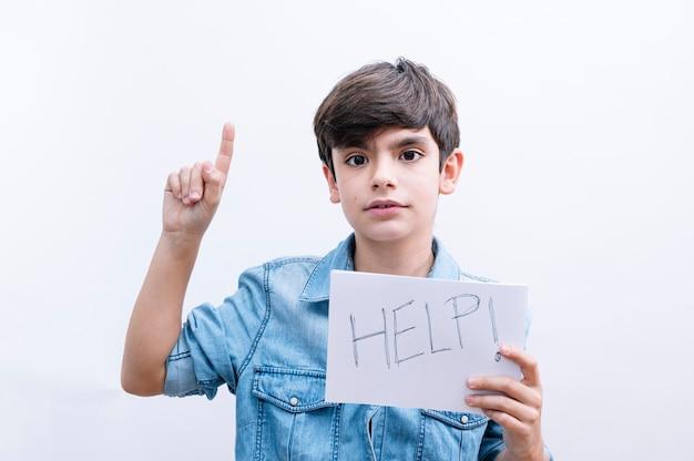 紙を持っている若い男の子の子供は、幸せそうな顔で指を指すアイデアや質問に驚いて保護を求めるヘルプメッセージで歌います、ナンバーワン