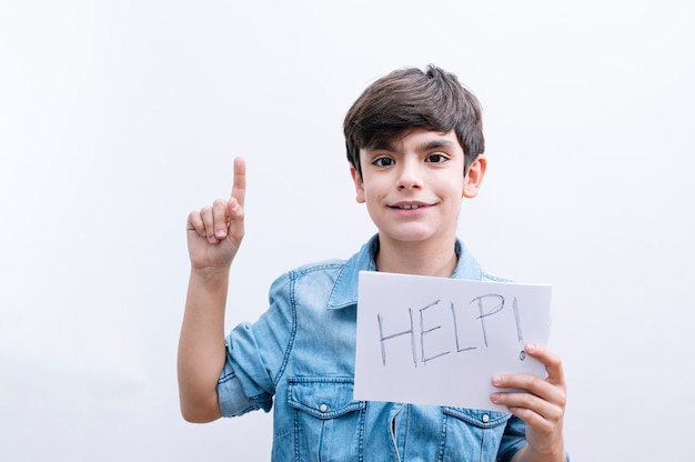 Young little boy kid holding paper sing with help message asking for protection surprised with an idea or question pointing finger with happy face, number one
